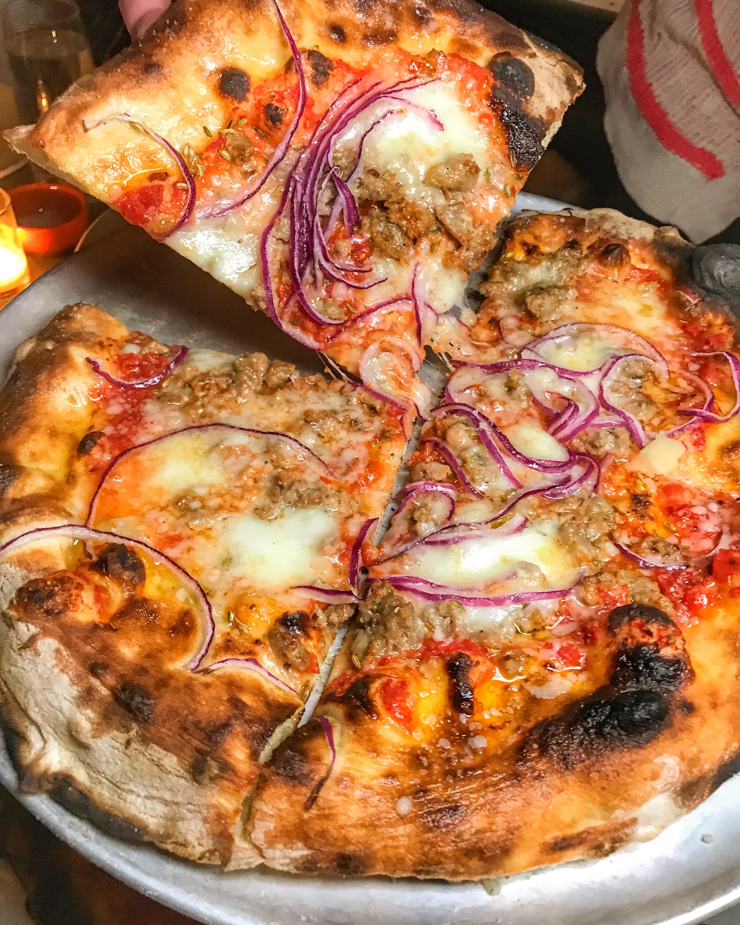 Let's talk about a beautiful pizza pie from Pizzeria Sirentta with tomato,  fennel sausage, onions, oregano, buffalo mozzarella.